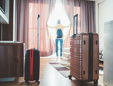 person in hotel room with luggage