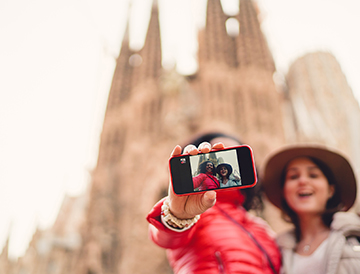 two women taking selfie in front of a building