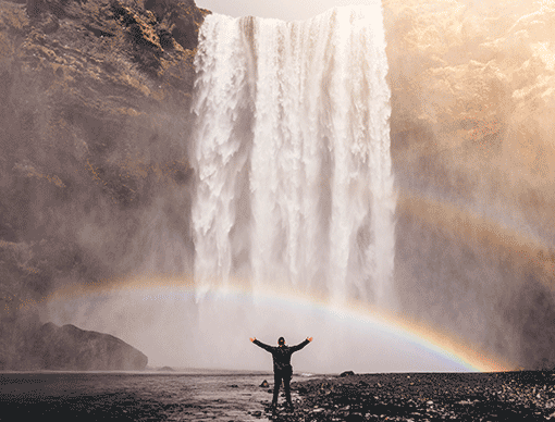 person in front of waterfall with a rainbow